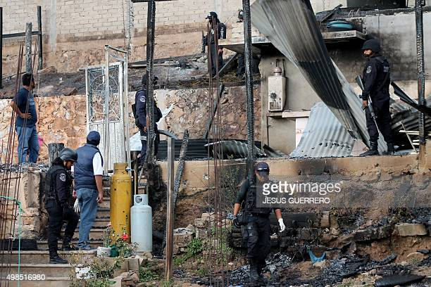 State and judicial police investigate a crime scene after a woman and three of her sons were killed by gunmen in an attack where three houses were...
