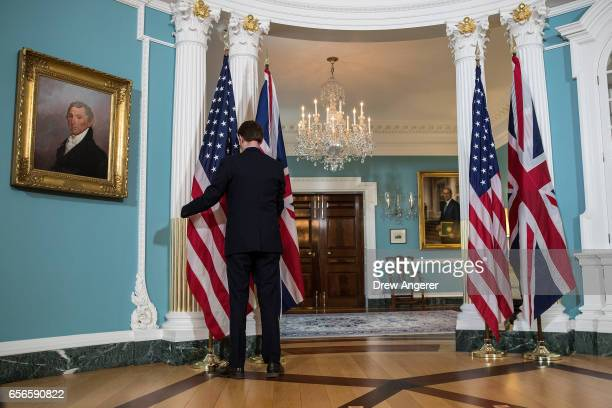 State Department staff member adjusts the US and British flags before a photo opportunity with Secretary of State Rex Tillerson and British Foreign...