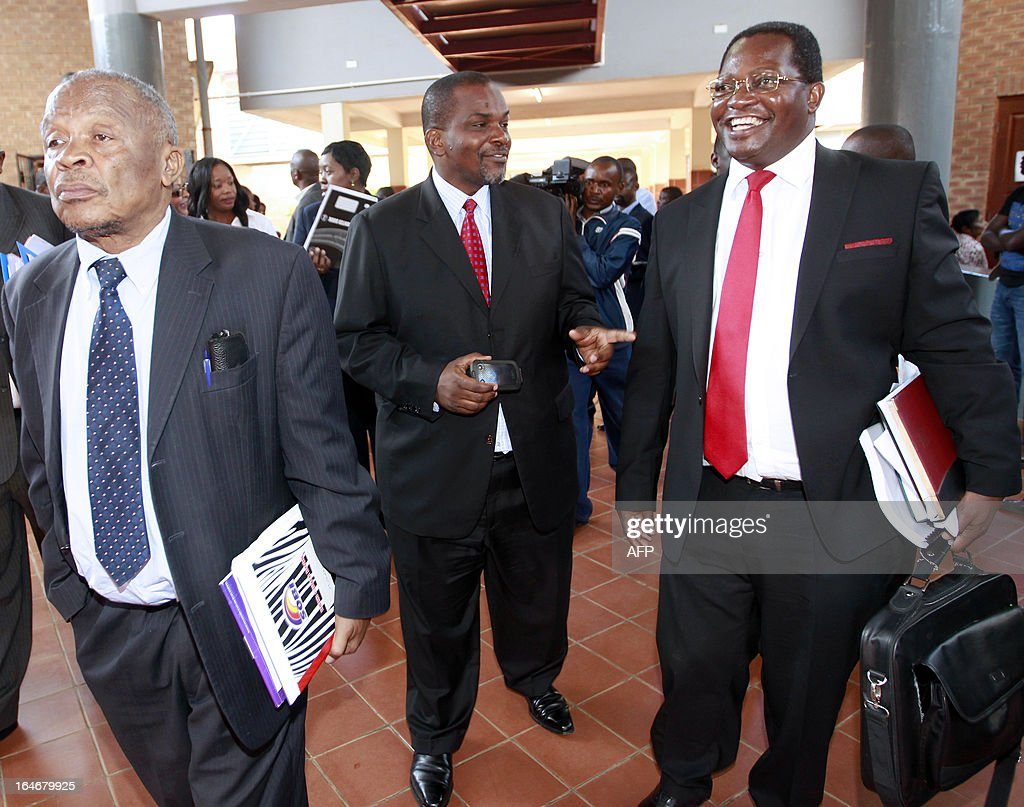 State Director of Public Prosecutions Mutembo Nchito (C) chats with former president Rupiah Banda's lawyers Erick Silwamba (R) and Patrick Mvunga (L) as they leave the Lusaka magistrate court on March 26, 2013 after Banda plead not guilty to a charge of abuse of power linked to an oil contract signed while he was in office. He was arrested on March 25, 2013 after being questioned by investigators over his role in a deal with a Nigerian firm. AFP PHOTO/JOSEPH MWENDA