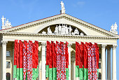 State flags of the Republic of Belarus against the backdrop of the Palace of Culture of Trade Unions in Minsk