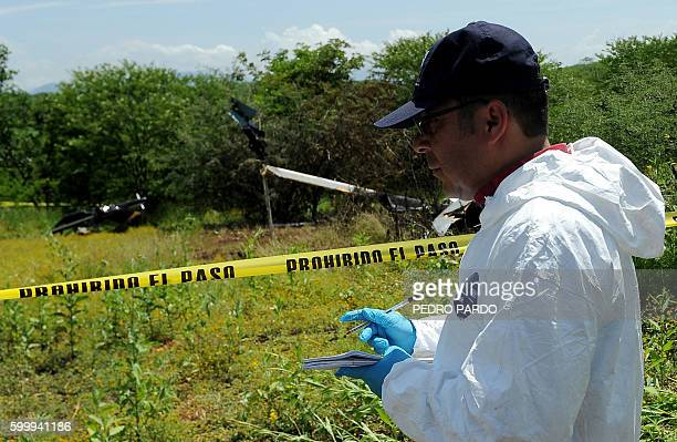 State forensic personnel work on the site where a police helicopter participating in an operation to capture leaders of an unidentified criminal...