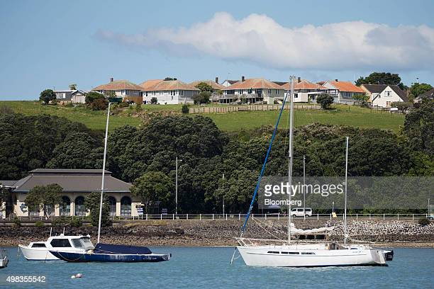 State houses stand on a hill in the suburb of Orakei as yachts are moored by the waterfront in Auckland New Zealand on Friday Nov 13 2015 State homes...