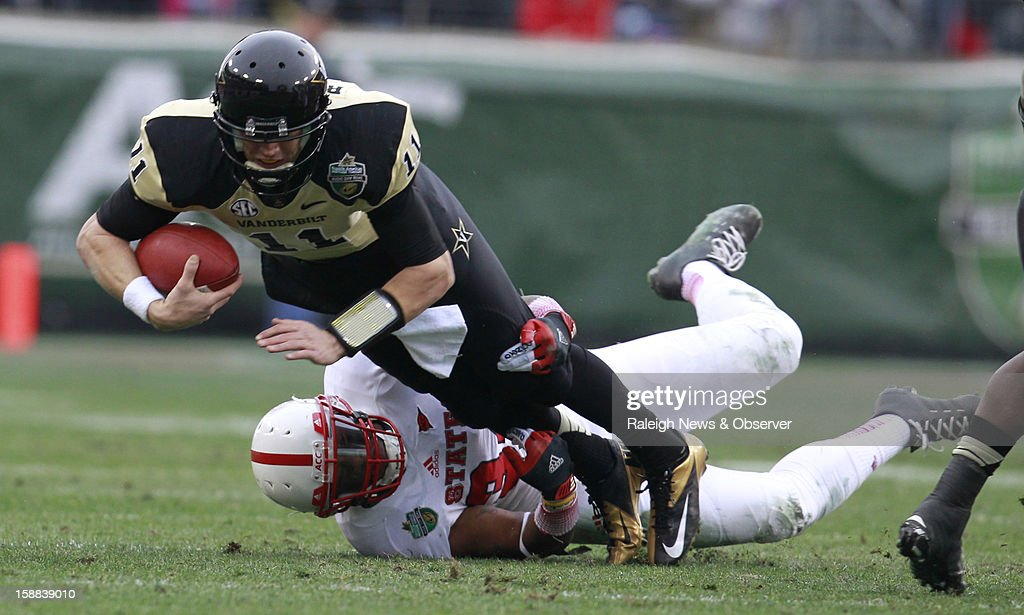 N.C. State linebacker Rickey Dowdy (34) tackles Vanderbilt quarterback Jordan Rodgers (11) during the first half of the Franklin American Mortgage Music City Bowl at LP Field in Nashville, Tennessee, Monday, December 31, 2012. The Vanderbilt Commodores defeated the N.C. State Wolfpack, 38-24.
