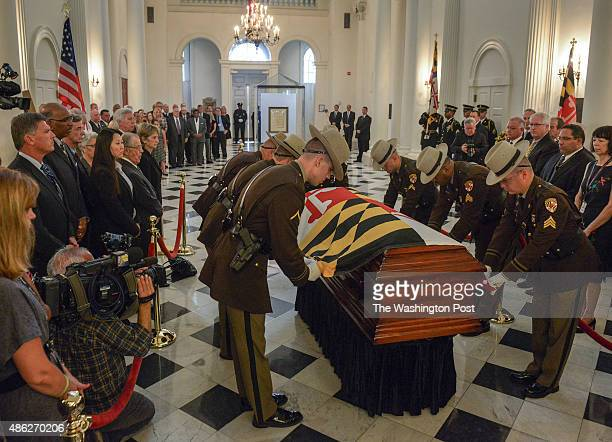 State police honor guards place the state flag over the casket containing former Governor Marvin Mandel's remains at the Maryland statehouse where he...