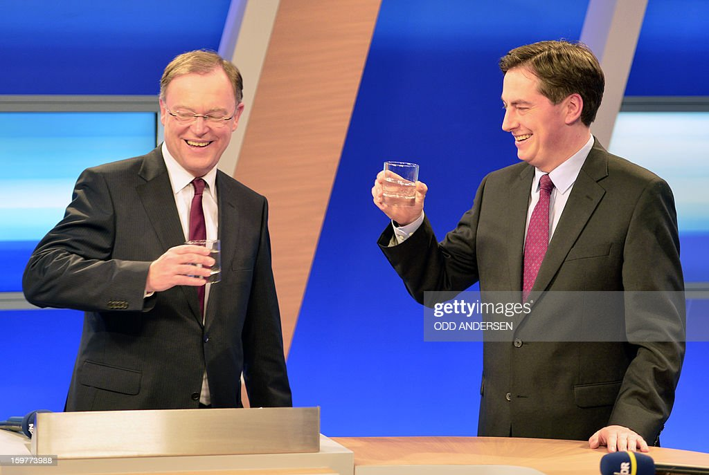 State premier of Lower Saxony David McAllister (R) and top candidate of the German party Social Democrats, SPD, Stephan Weil raise their glasses during a talk in a TV studio at the Landtag regional parliament in Hanover on January 20, 2013 on polling day of the local elections in the central German state of Lower Saxony. The vote is largely seen as a test run for Chancellor Angela Merkel, her rivals and would-be heirs, eight months before nationwide polls. German Chancellor Angela Merkel's party was ahead after the first state poll in a general election year, exit polls indicated, but it was unclear whether its coalition would cling to power. AFP PHOTO / ODD ANDERSEN