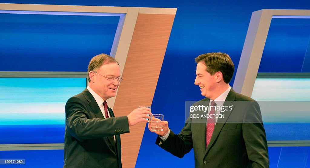 State premier of Lower Saxony David McAllister (R) and top candidate of the German party Social Democrats, SPD, Stephan Weil raise their glasses during a talk in a TV studio at the Landtag regional parliament in Hanover on January 20, 2013 on polling day of the local elections in the central German state of Lower Saxony. The vote is largely seen as a test run for Chancellor Angela Merkel, her rivals and would-be heirs, eight months before nationwide polls. German Chancellor Angela Merkel's party was ahead after the first state poll in a general election year, exit polls indicated, but it was unclear whether its coalition would cling to power.