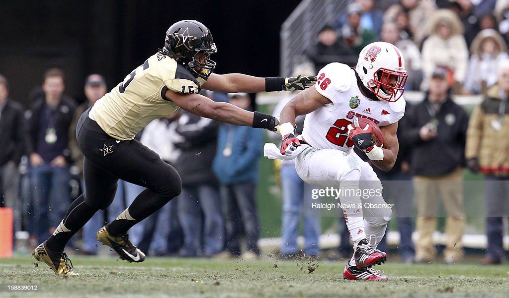 N.C. State running back Tony Creecy (26) runs by Vanderbilt linebacker Archibald Barnes (15) during the first half of the Franklin American Mortgage Music City Bowl at LP Field in Nashville, Tennessee, Monday, December 31, 2012. The Vanderbilt Commodores defeated the N.C. State Wolfpack, 38-24.