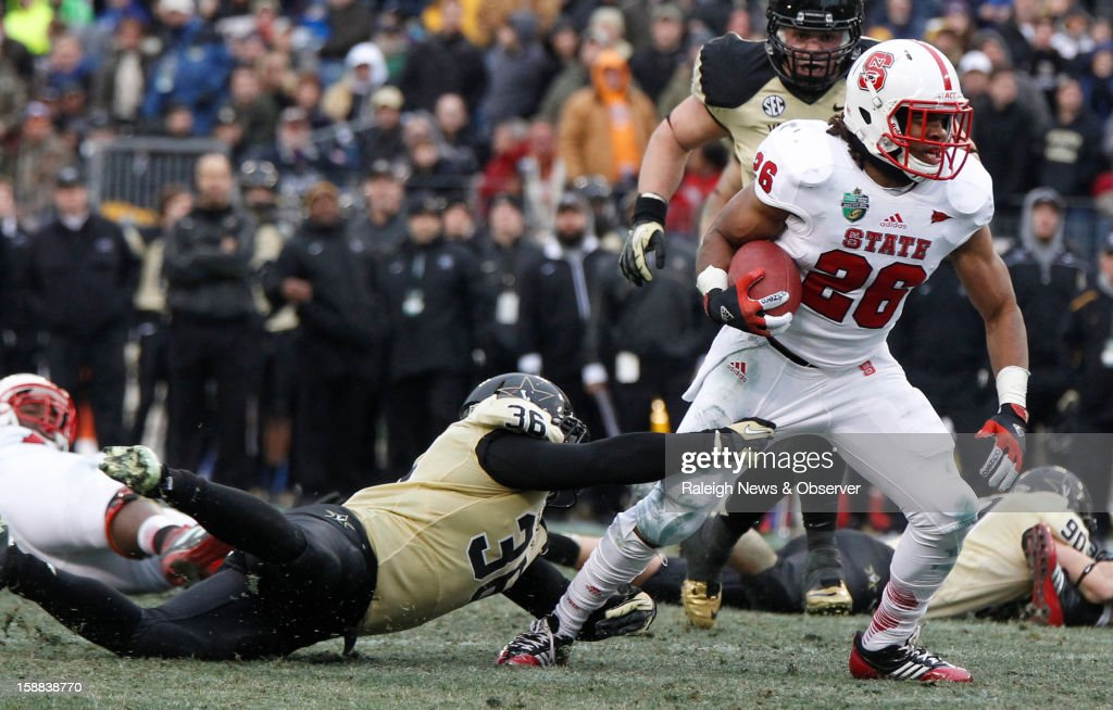 N.C. State running back Tony Creecy (26) tries to break free from Vanderbilt linebacker Chase Garnham (36) during the second half of the Franklin American Mortgage Music City Bowl at LP Field in Nashville, Tennessee, Monday, December 31, 2012. The Vanderbilt Commodores defeated the N.C. State Wolfpack, 38-24.