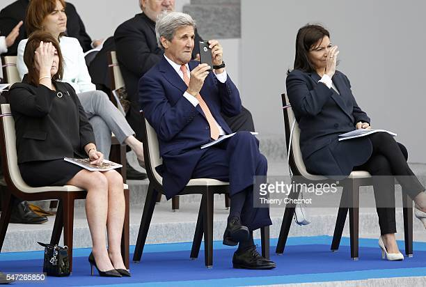State Secretary John Kerry takes a picture during the annual Bastille Day military parade on the ChampsElysees avenue on July 14 2016 in Paris France...