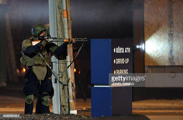 A state trooper aims his gun at protesters in Ferguson Missouri on November 25 2014 during a demonstration a day after violent protests and looting...