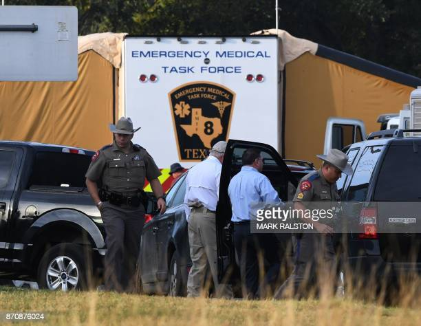 State troopers and other officials gather at the entrance to the First Baptist Church after a mass shooting that killed 26 people in Sutherland...