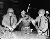 State Troopers arrest a man for breaking a curfew established in Rochester during three days of riots New York circa 1960s