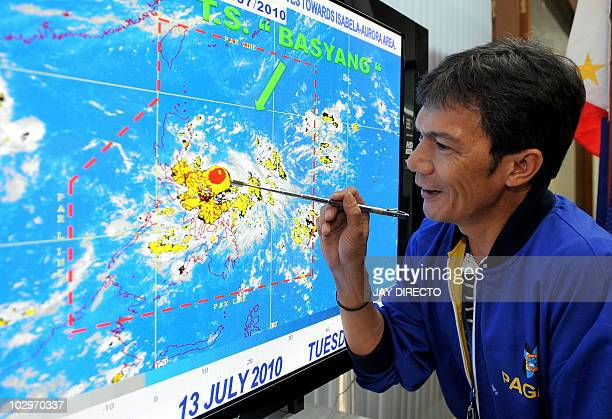 State weather forecaster Rene Paciente shows the movement of Typhoon Conson at the Philippine Atmospheric Geophysical and Astronomical Services...