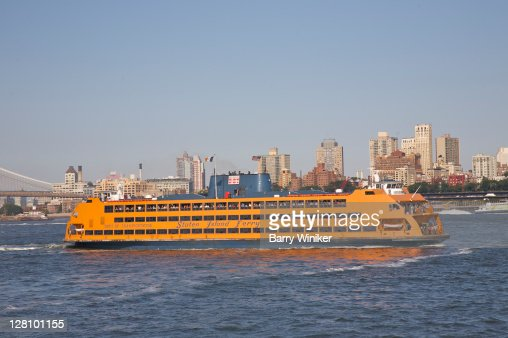 Staten Island Ferry leaving slip in Lower Manhattan with Brooklyn Heights in background, NY