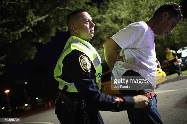 City of North Miami Beach police officer Ray DeJesus Jr searches a person under arrest for suspicion of driving under the influence during a DUI...