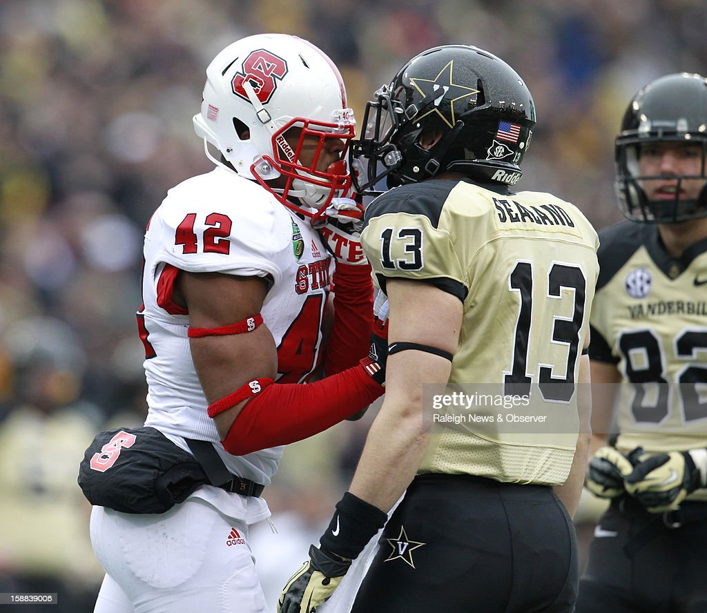 N.C. State's M.J. Salahuddin (42) has words with Vanderbilt's Jake Sealand (13) during the first half of the Franklin American Mortgage Music City Bowl at LP Field in Nashville, Tennessee, Monday, December 31, 2012. The Vanderbilt Commodores defeated the N.C. State Wolfpack, 38-24.