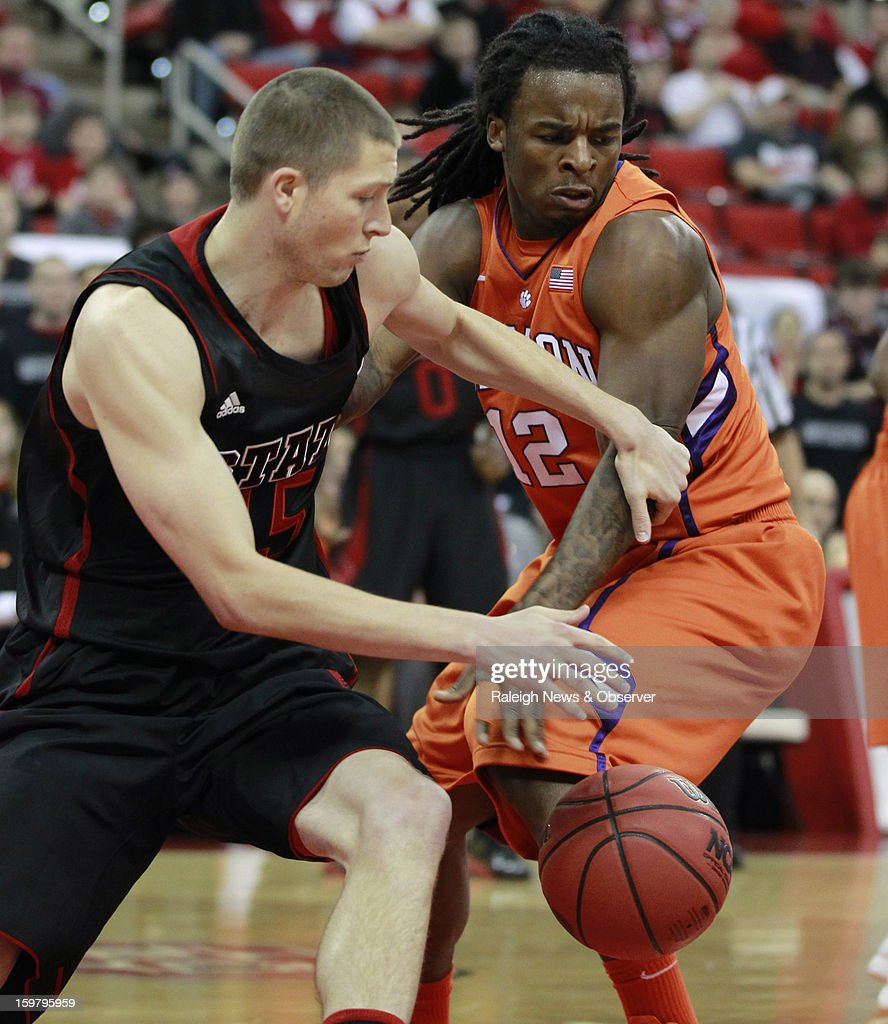 N.C. State's Scott Wood (15) and Clemson's Rod Hall (12) fight for a loose ball during the first half of a men's college basketball game at PNC Arena on Sunday, January 20, 2013, in Raleigh, North Carolina.
