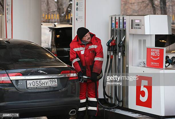 A station attendant refuels a Jaguar XF automobile at a fuel pump on the forecourt of an OAO Lukoil gas station in Moscow Russia on Tuesday Dec 2...