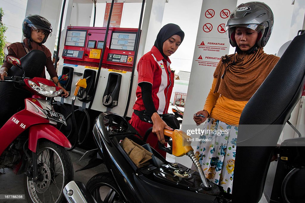 A station attendant refuels a moped at a fuel station on April 30, 2013 in Yogyakarta, Indonesia. The Indonesian government is considering raising fuel prices for all vehicle types in an attempt to free up funds for infrastructure and spur growth.