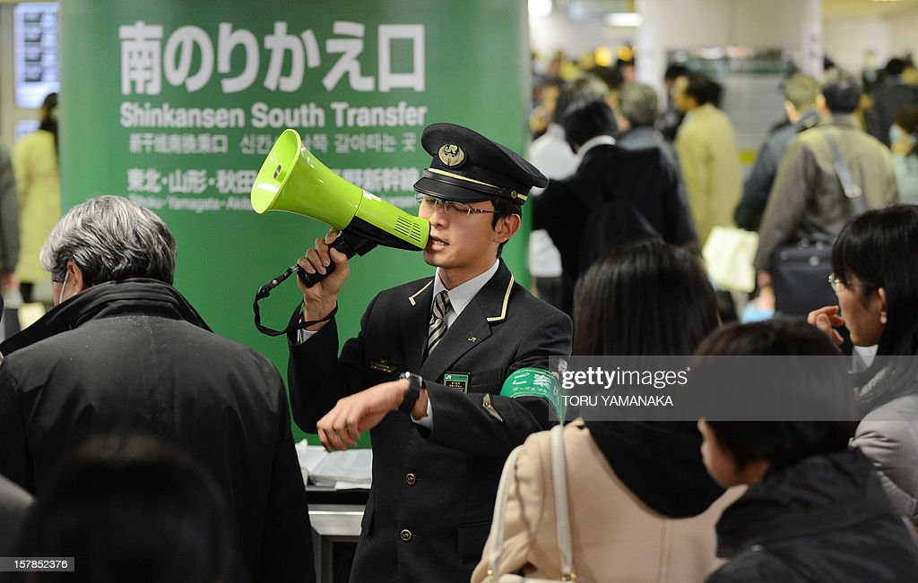 A station attendant (C) uses a loudspeaker to explain the train service situations for the Tohoku Shinkansen (bullet train) which connects Tokyo and northern Japan at Tokyo Station on December 7, 2012 following a 7.3 earthquake and tsunami alert. A one metre-high tsunami hit northeast Japan after a powerful undersea quake struck off the coast which was devastated in last year's quake-tsunami disaster. AFP PHOTO/Toru YAMANAKA