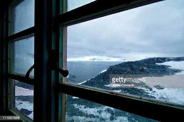 An icy landscape from an abandoned Antarctic research station window.