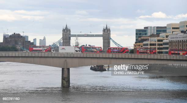 Stationary buses and a a large white van operated by the police to remove the van used in the attack on London Bridge are seen on London Bridge in...