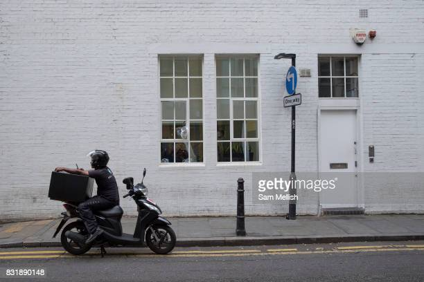 A stationary deliveroo motorcyclist looking at his mobile phone near Hoxton Square on 5th August 2016 in London United Kingdom Hoxton Square is a...