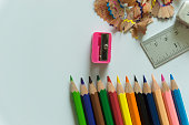 Stationery set for drawing on white background include crayons, ruler, eraser, sharpener and debris from the sharpening