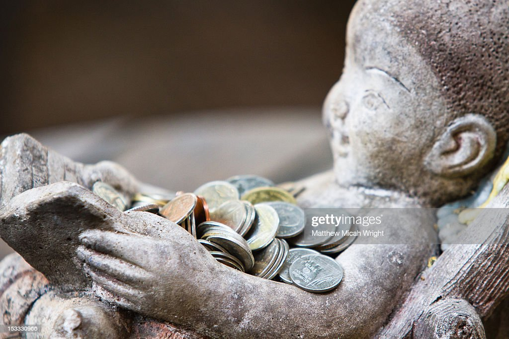 A statue collects coins for wishes. : Stock Photo