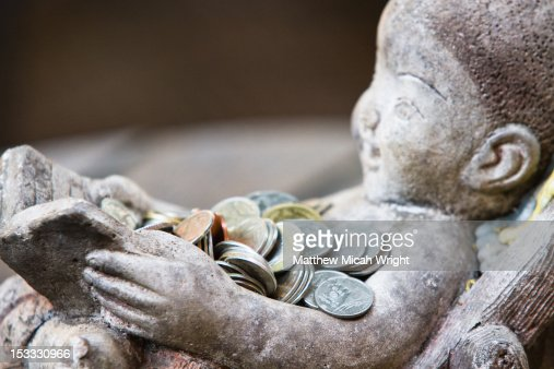 A statue collects coins for wishes. : Foto de stock