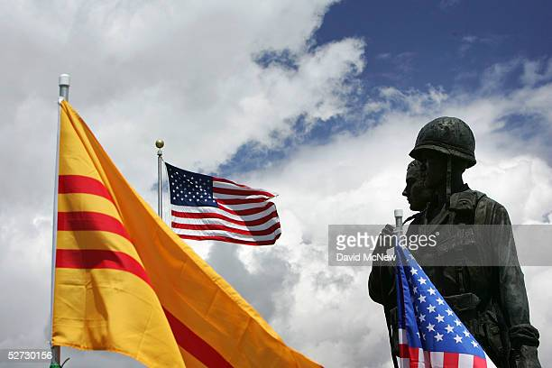 A statue depicting an American and South Vietnamese soldier is surrounded by American and oldstyle Vietnamese flags at the Vietnam War Memorial on...