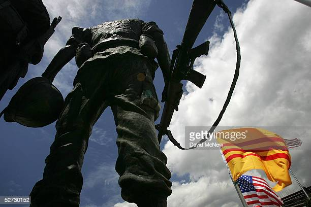 A statue depicting an American soldier is surrounded by oldstyle Vietnamese and American flags at the Vietnam War Memorial on April 28 2005 near the...