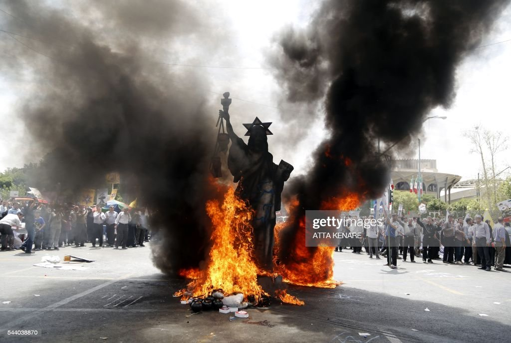 A statute depicting US' Statue of Liberty decorated with a Star of David on its head is set ablaze by Iranian protestors during a parade marking al-Quds (Jerusalem) Day in Tehran on July 01, 2016. Tens of thousands joined pro-Palestinian rallies in Tehran, as the annual Quds Day protests take on broader meaning for a region mired in bitter disputes and war. KENARE