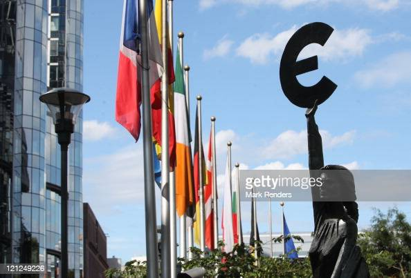 A statue holding the symbol of the Euro the European common currency stands in front of the European Parliament building on August 16 and 2011 in...