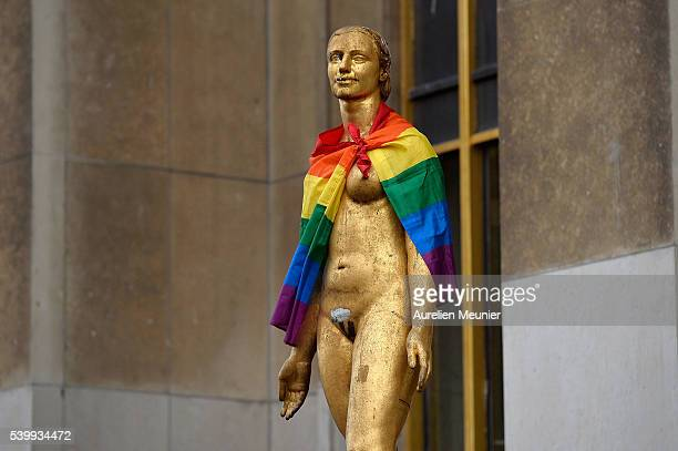 A statue is draped with the gay pride flag as people gather in front of the Eiffel Tower on Place du Trocadero during the vigil for victims of the...