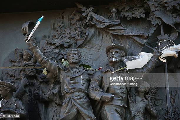 A statue is modified with a pen in a show of defiance as demonstrators gather in Place de la Republique prior to a mass unity rally to be held in...