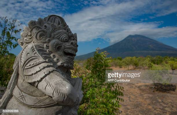 A statue is placed on the roadside in Karangasem on Bali island on October 3 as Mount Agung volcano is seen in the background Thousands of residents...