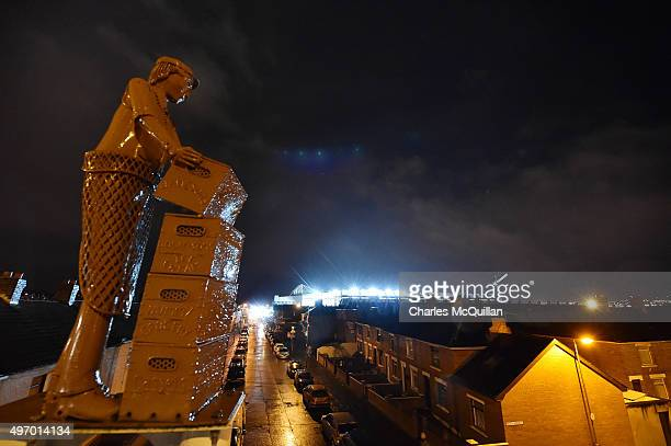 A statue of a baker watches over the national football stadium which can be seen illuminating sidestreets around the ground before the international...