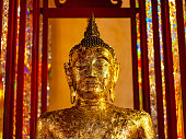 Statue of a Buddha image covered in gold leaf in the grounds of a typical Thai Buddhist temple. Selective focus with focus on the eyes.