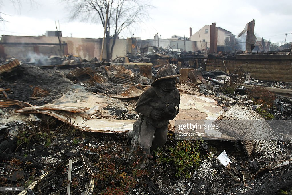 A statue of a firefighter stands in front of a home destroyed by fire after Hurricane Sandy on October 30, 2012 in the Rockaway section of the Queens borough of New York City. At least 40 people were reportedly killed in the U.S. by Sandy as millions of people in the eastern United States have awoken to widespread power outages, flooded homes and downed trees. New York City was hit especially hard with wide spread power outages and significant flooding in parts of the city.