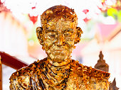 Statue of a revered abbot covered in gold leaf in the grounds of a typical Thai Buddhist temple.
