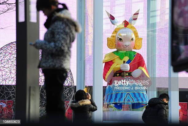 A statue of a variation of traditional Beijing folk icon Lord Rabbit is displayed behind glass enclosure at a shopping mall in Beijing on January 31...