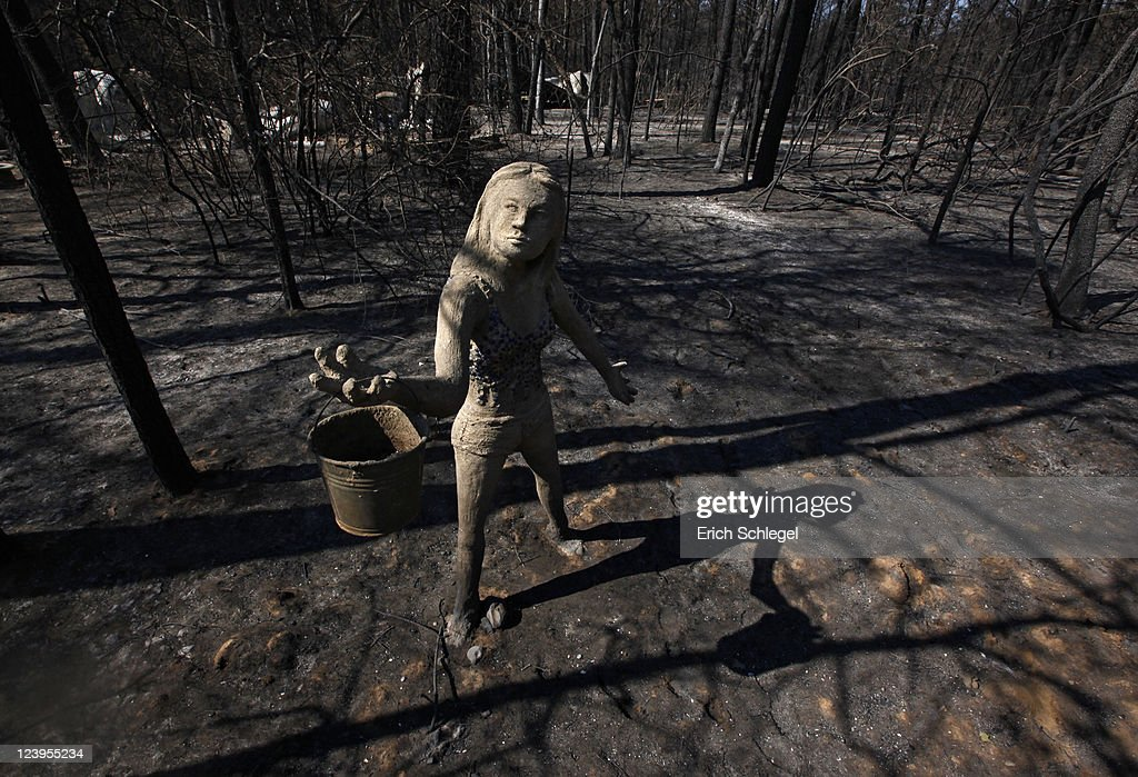 A statue of a woman holding a water bucket stands in front of the remnants of a burned down home on the east side of Lake Bastop on September 6, 2011 outside Bastrop, Texas. Several large wildfires have been devastating Bastrop County for the last two days.