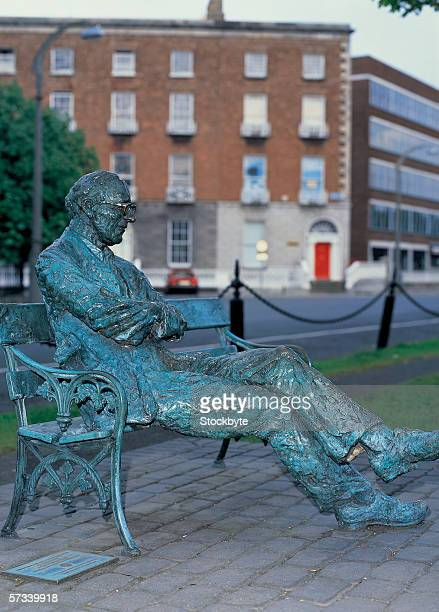statue of an old man sitting on a park bench