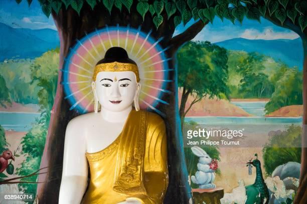 Statue of Buddha by a painted wall near Kyaik Than Lan Pagoda, Mawlamyine, Mon State, Southern Myanmar (Burma)