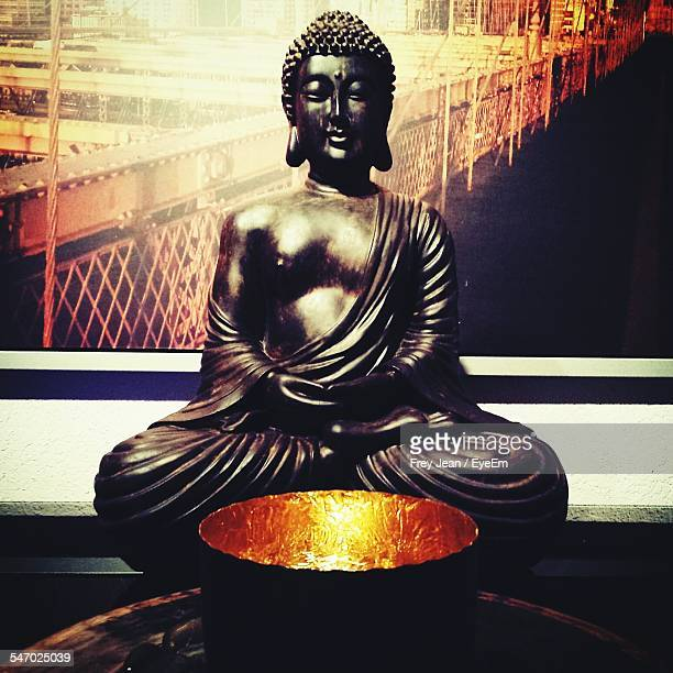 Statue Of Buddha By Illuminated Bowl