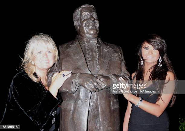 A statue of comedian Les Dawson is unveiled by his widow Tracy Dawson left and daughter Charlotte at St Annes Pier Lytham St Annes Lancashire