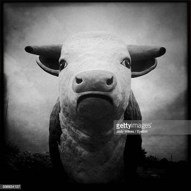 Statue Of Cow Against Cloudy Sky