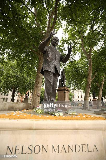 A statue of former South African President Nelson Mandela with flowers laid at its base in Parliament Square on June 27 2013 in London England South...
