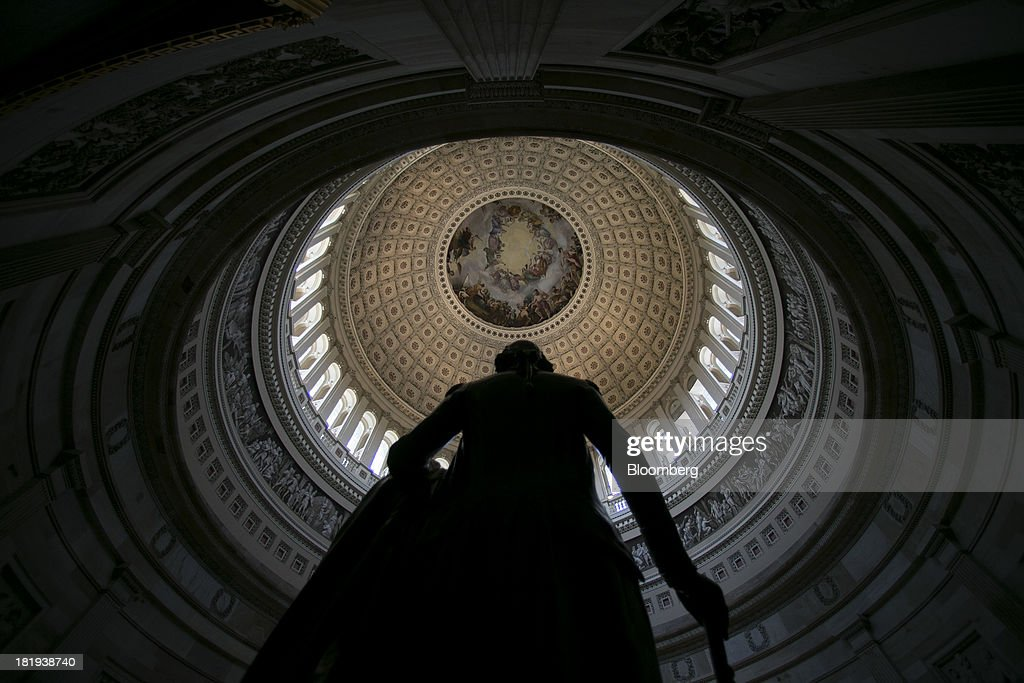 A statue of George Washington stands in the U.S. Capitol Rotunda below the Apotheosis of Washington fresco in in Washington, D.C., U.S., on Thursday, Sept. 26, 2013. The Senate is accelerating debate on a bill that would avert a U.S. government shutdown as Senate Republicans sought to buy time for their House counterparts to take another swipe at President Barack Obama's health-care law. Photographer: Andrew Harrer/Bloomberg via Getty Images